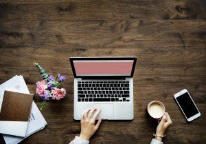 女性がパソコンの前でコーヒーを持つ画像