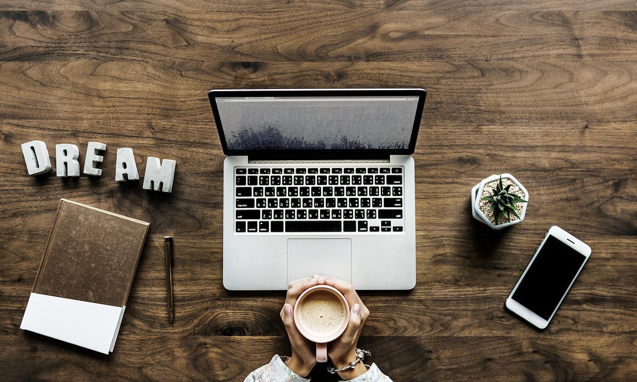 パソコンの前でコーヒーを持っている男性が夢を語っている画像