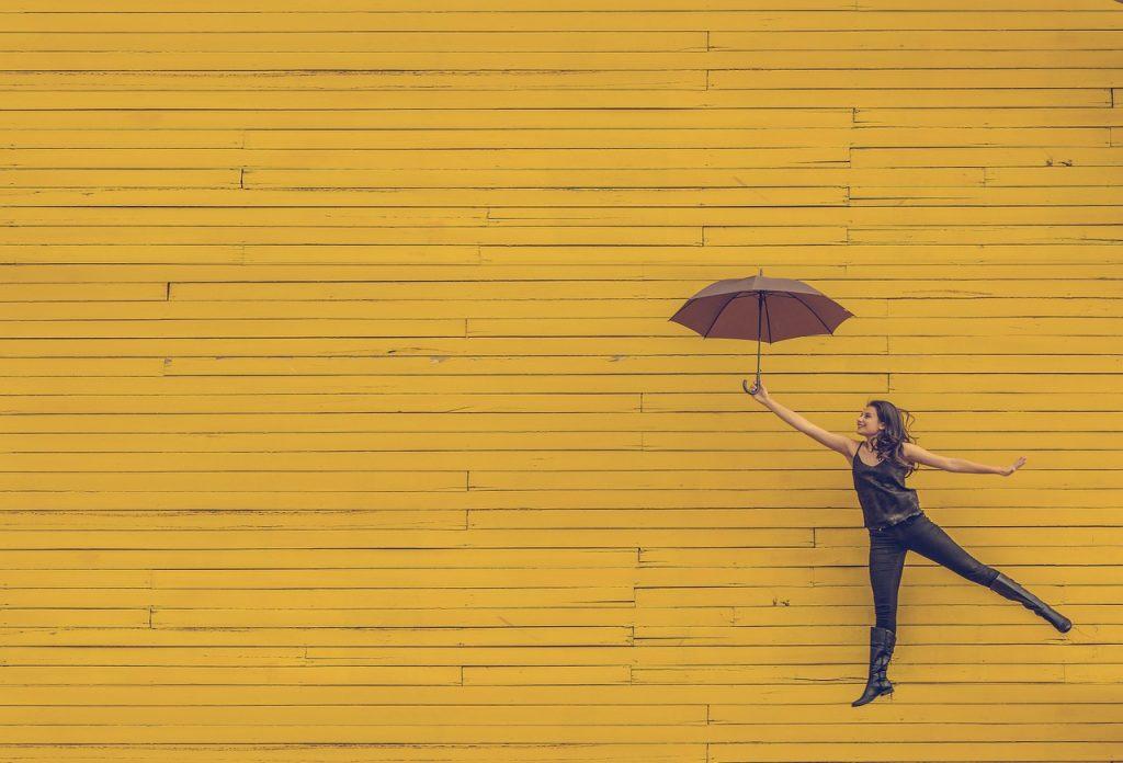 黄色をバックに傘を持ちながらジャンプする女性の画像