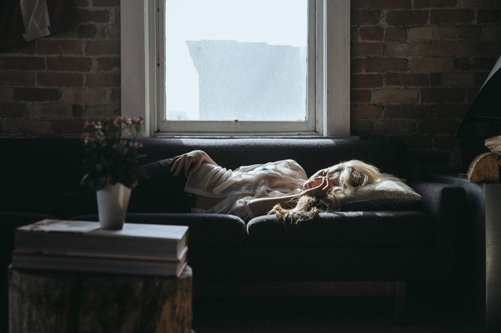 女性が疲れて横たわる画像悲しそう