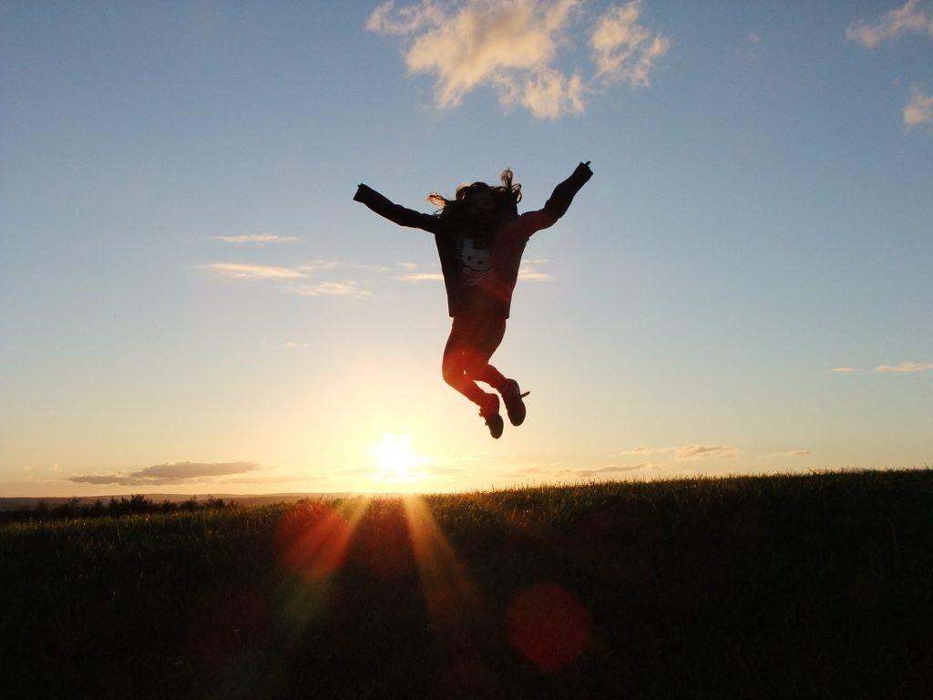 地平線が見える場所でジャンプする女性の画像