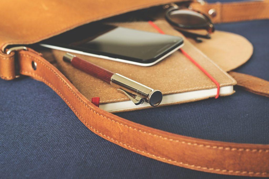 鞄にノートとスマホとペンとサングラスが入っている画像