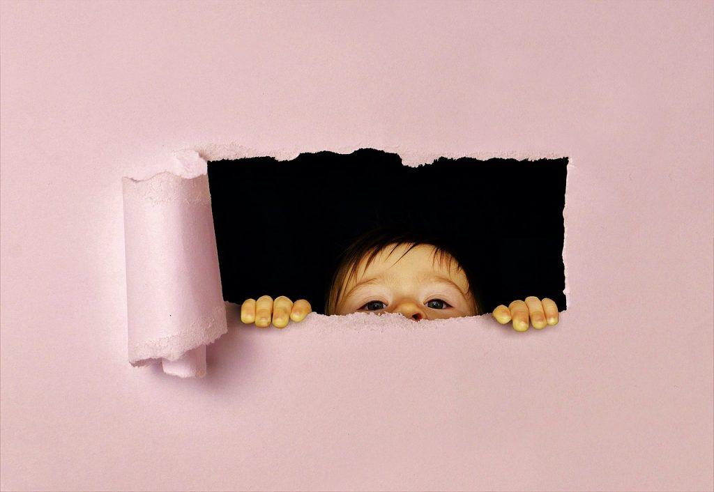 壁から男の子が顔を出している画像