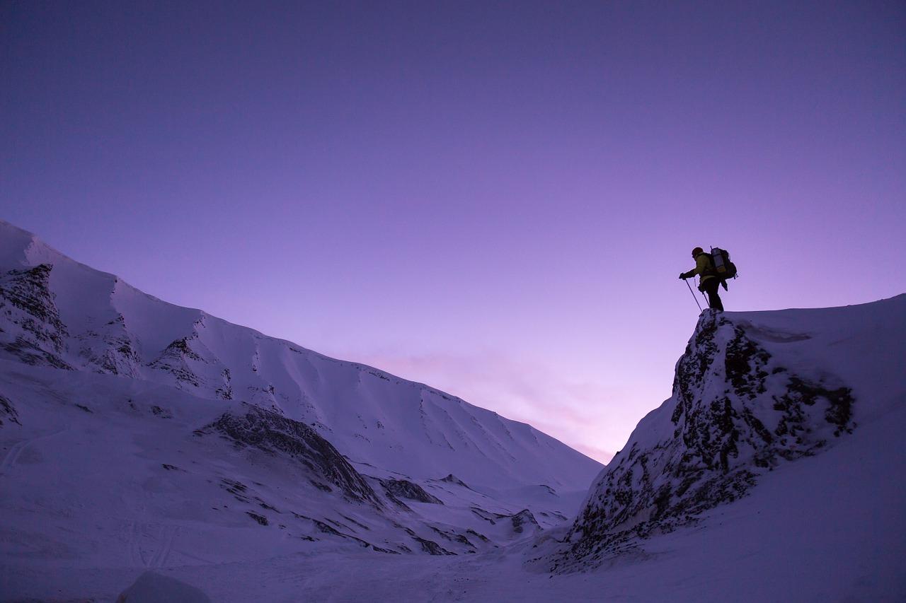 厳しい雪山を男性が登っている画像