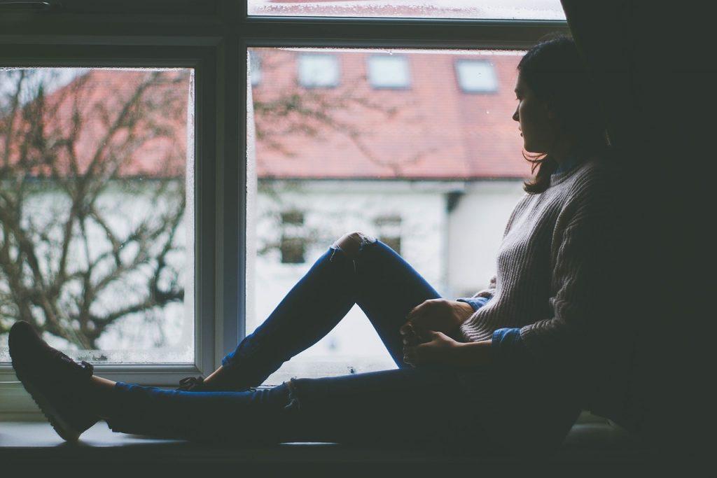 悲しそうに窓によりかかる女性の画像