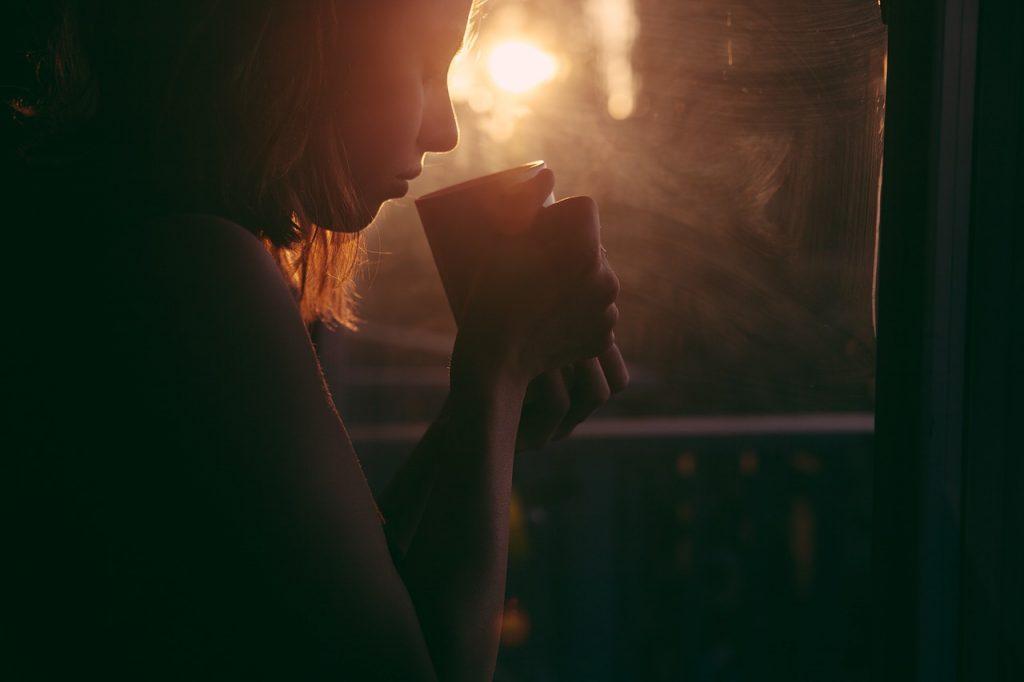 悲しそうにマグカップを持った女性の画像